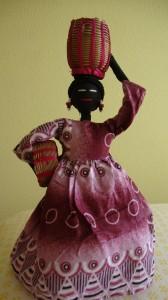 Esta muñeca representa a la mujer de L´Ouest de Camerún que se dirige al campo para recoger sus frutas y verduras que las llevará a su casa en el cesto que lleva en su cabeza. La cesta más pequeña la deja para que su hijo la ayude...
